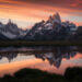 Cerro Torre and Fitz Roy reflected in an infinity pool during an intense sunset.